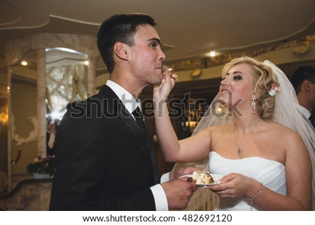Bride is feeding a groom with the wedding cake