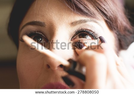 Bride is getting professional make up for her wedding day,putting on mascara. - stock photo
