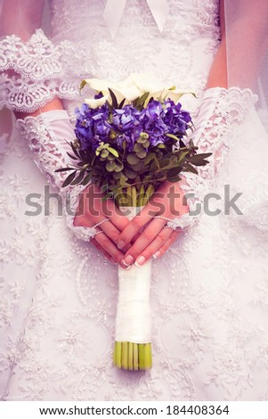Bride is holding a bouquet of blue hydrangeas with white calla lilies - stock photo
