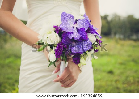 Bride is holding a bouquet of lilac in the hands on a green background