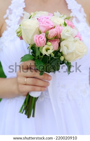 Bride is holding beautiful bright wedding bouquet - stock photo
