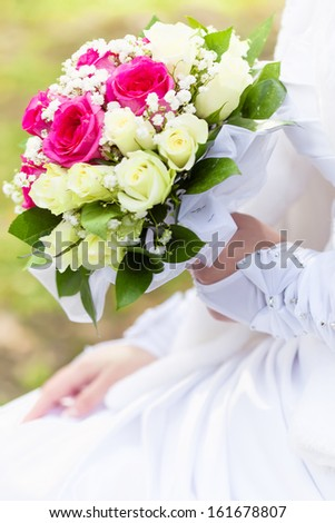 Bride is holding her bouquet in hands. Close-up
