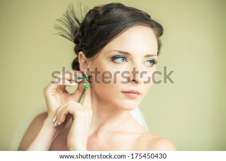 Bride is looking away and straightens earrings - stock photo