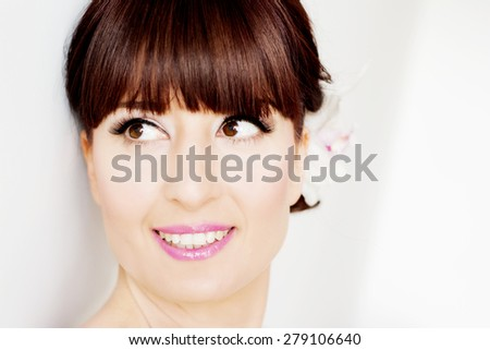 Bride is posing after getting professional make up for her wedding day, beautiful face closeup.Bride has bangs. - stock photo