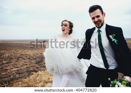 Bride is running with the funny face - stock photo
