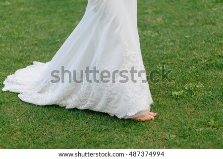 Bride is walking on the fresh green grass