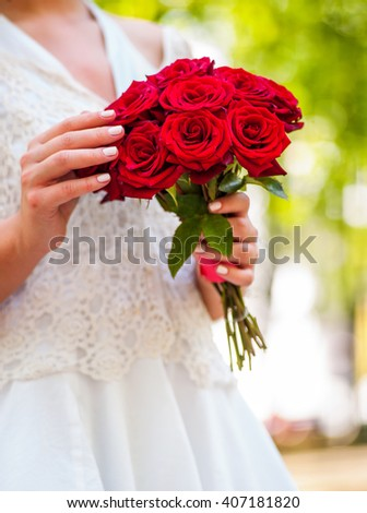 Bride keeps red rose flowers bouquet.  - stock photo