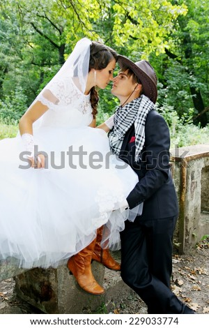 Bride kissing groom in a cowboy hat - stock photo