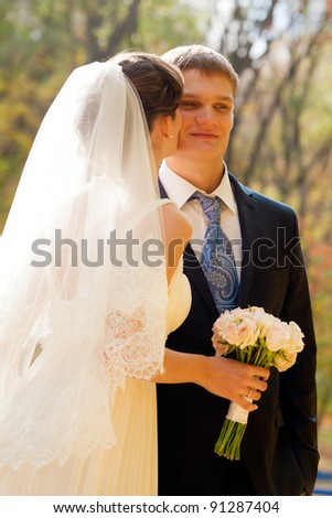 Bride kissing her groom in the park - stock photo