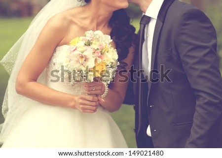 Bride kissing the groom and holding a wedding bouquet - stock photo