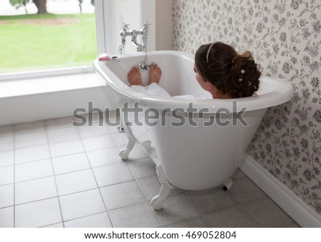 Bride laid in the bath on her wedding day, taking a moment to herself.