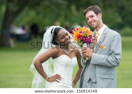 Bride looking at groom holding banquet of flowers on wedding day - stock photo