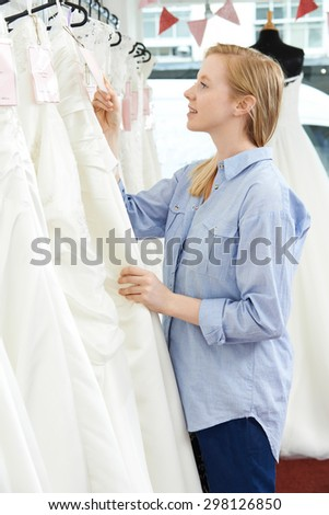 Bride Looking At Price Tag On Wedding Dress In Bridal Boutique - stock photo