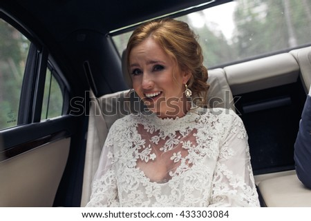Bride looks funny sitting on the back seat in the car - stock photo