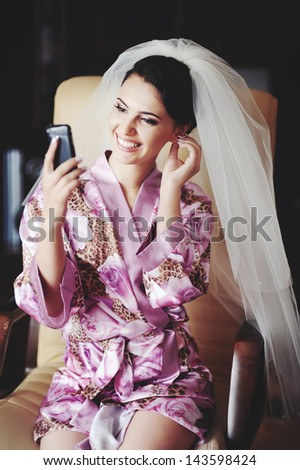 bride looks in to mobile phone using at as a mirror, happy bridal morning - stock photo