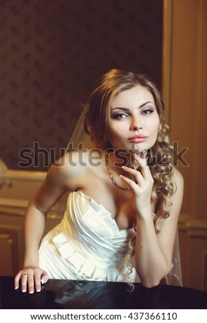 Bride looks stunning leaning on the black piano in a hall