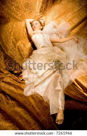 bride lying down in wedding dress, studio shot, - stock photo