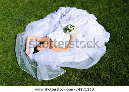 Bride lying on a wedding dress on the grass. - stock photo