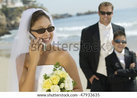 Bride on Cell Phone With Groom and Brother - stock photo