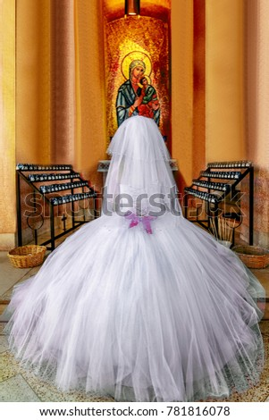 Bride on her knees in a church in front of the icon of the mother of god