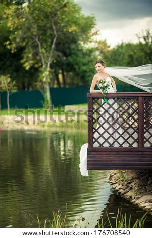 Bride on the banks of the romantic lake. - stock photo