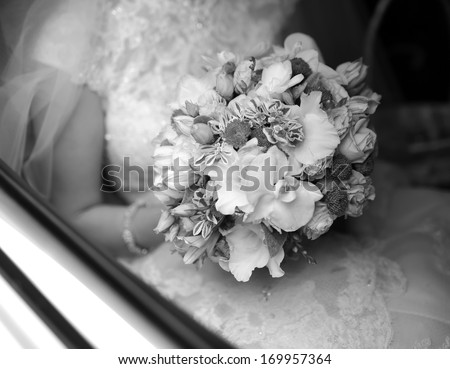 Bride on wedding day in car with bouquet - stock photo
