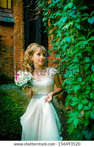 Bride over brick and wall outdoors  - stock photo