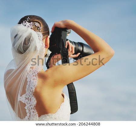 Bride photographer. Caucasian young newlywed  walking with camera. - stock photo
