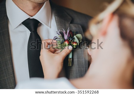 Bride pinning boutonniere on groom's suit of pink flowers and green