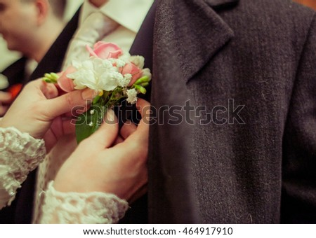 Bride pins a boutonniere on groom's tuxedo