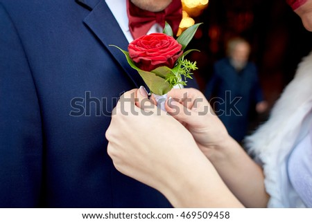 Bride pins red rose boutonniere to groom's blue jacket