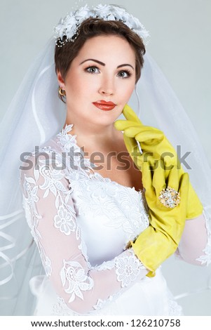 Bride posing with yellow rubber household gloves - stock photo