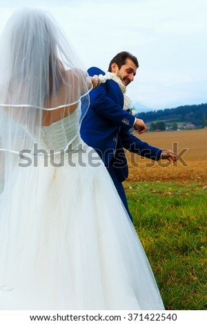 bride pulling her groom to her with a rope - funny wedding concept - stock photo