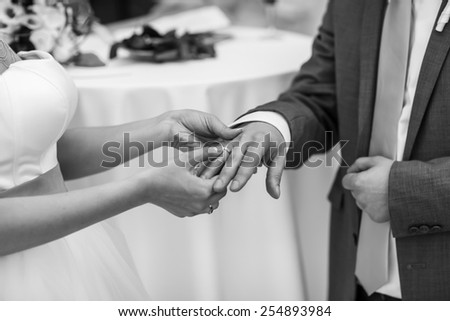 Bride puts a wedding ring on husband's finger. In black and white colors.