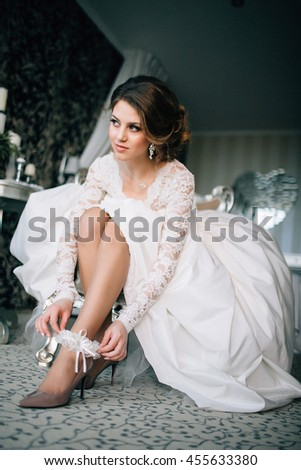 Bride puts on a shoe to a foot
