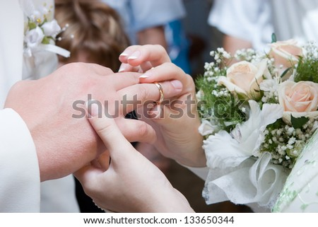bride puts on a wedding ring to a groom - stock photo