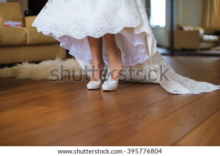 Bride puts on on a shoe to a foot standing in a room on a brown floor. Beautiful wedding white dress.