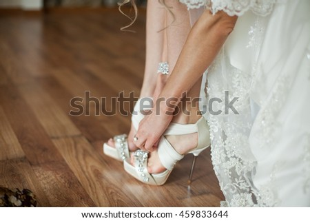 Bride puts on open toe wedding shoes
