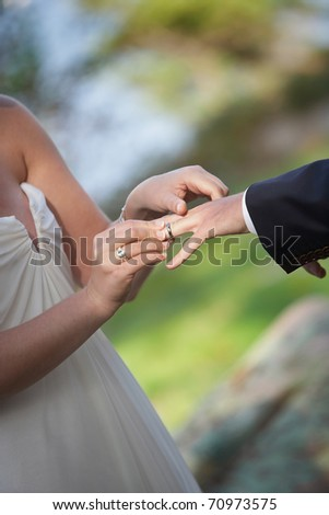 Bride putting a ring on groom's finger at outdoor wedding ceremony