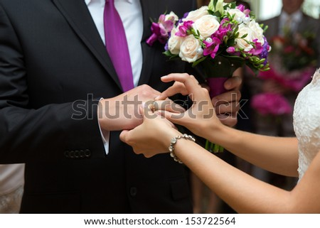 Bride putting a ring on groom's finger during wedding ceremony - stock photo