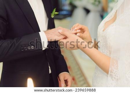 bride putting on golden ring on groom's finger - stock photo
