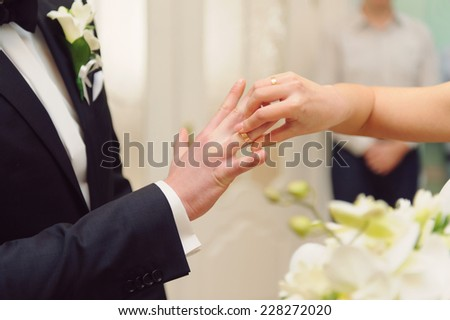 bride putting on wedding ring on groom's finger - stock photo