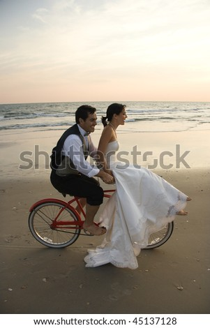 Bride rides the handle bars of a bicycle being driven by her groom on the beach. Vertical shot.