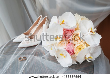 Bride's accessories - bouquet, wedding rings and shoes. Floral composition with roses and orchids.