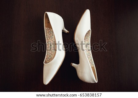 Bride's beige shoes lie on wooden table