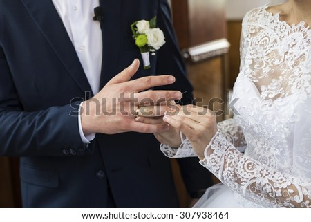 bride's hand putting a wedding ring on the groom's finger - stock photo