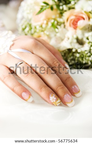 Bride's hand with golden ring and bouquet