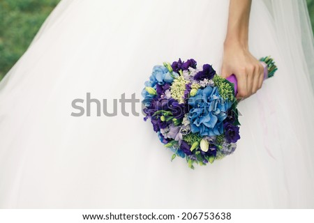 Bride's hand with wedding bouquet of blue flowers over white vapory dress and green lawn. Vintage style. Close up. Copy-space. Outdoor shot - stock photo
