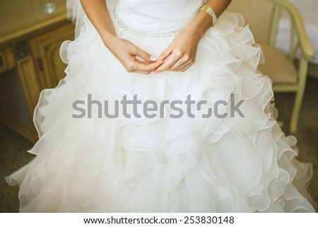bride's Hands on white dress - stock photo