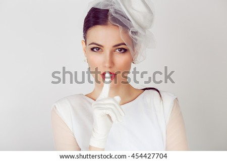 Bride shh Woman wide eyed asking for silence secrecy with finger on lips hush hand gesture white background wall Pretty girl placing fingers on lips shhh sign symbol Negative emotion facial expression - stock photo